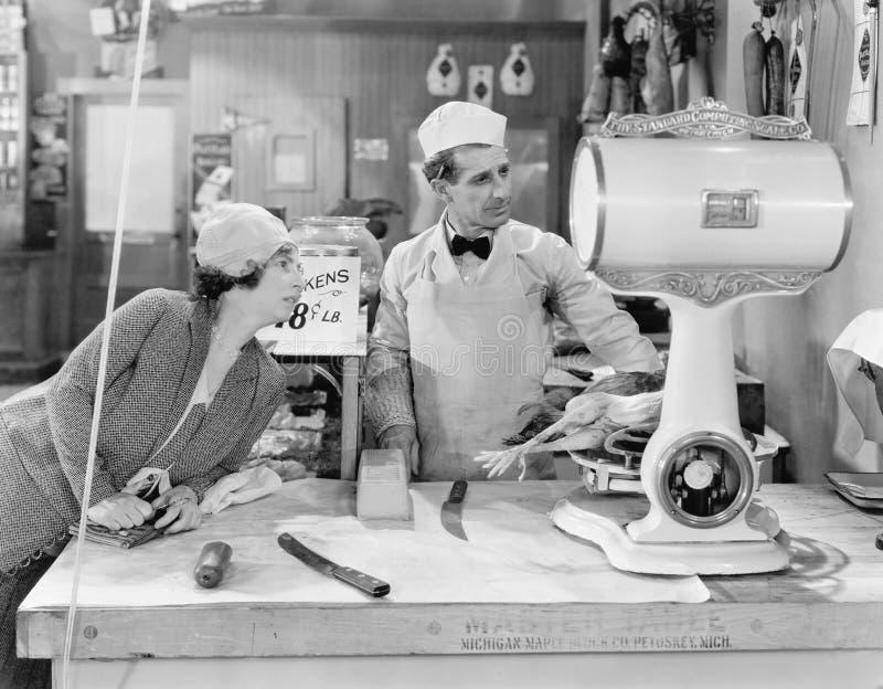 Mujer que se coloca en una tienda del carnicero que mira la escala (todas las personas representadas no son vivas más largo y nin fotos de archivo