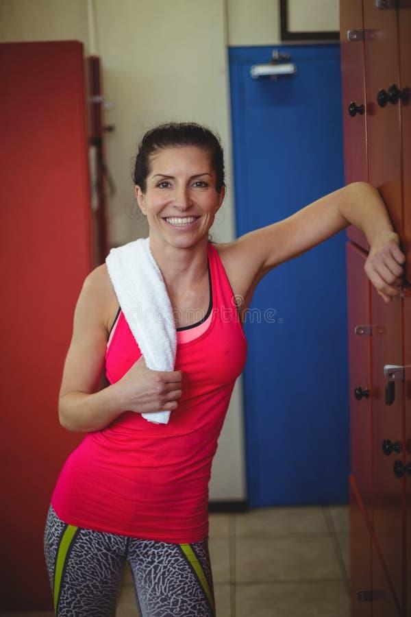 Mujer que se coloca en vestuario del gimnasio después de entrenamiento imagen de archivo libre de regalías
