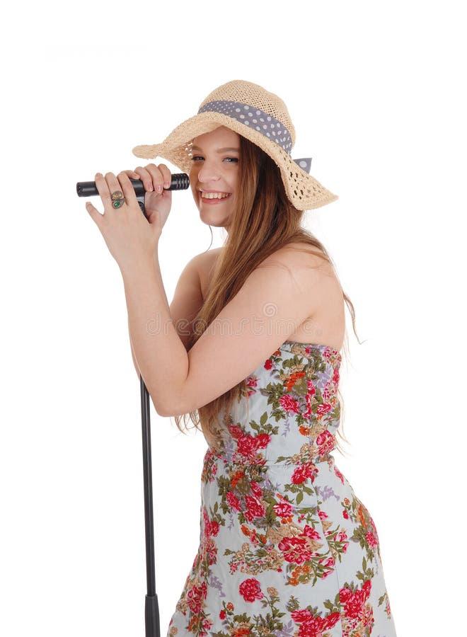 Mujer que se coloca que sostiene el micrófono imagenes de archivo