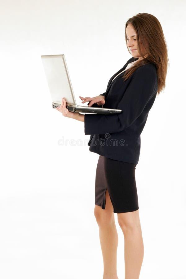 Mujer que se coloca y que trabaja con el ordenador portátil fotos de archivo libres de regalías