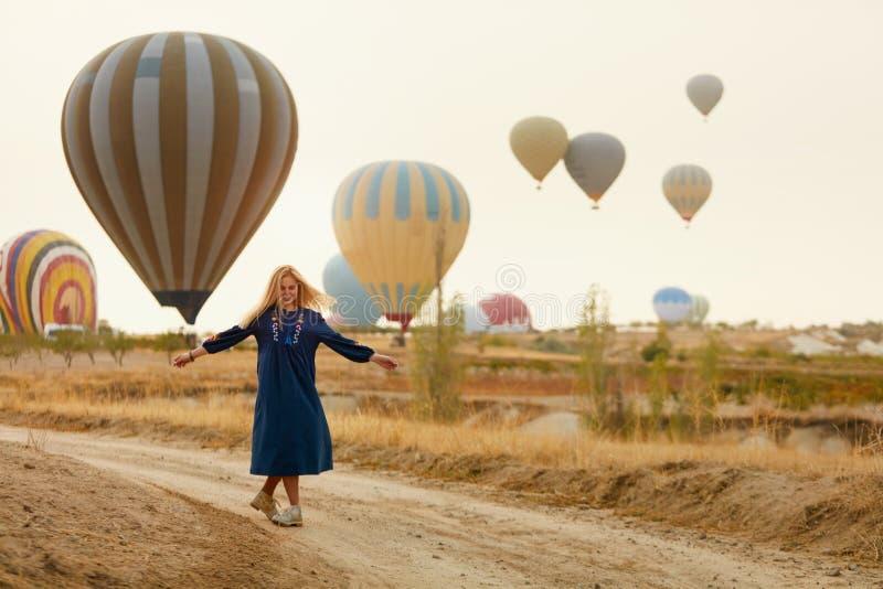 Mujer que se divierte con volar los globos del aire caliente en fondo imagen de archivo libre de regalías