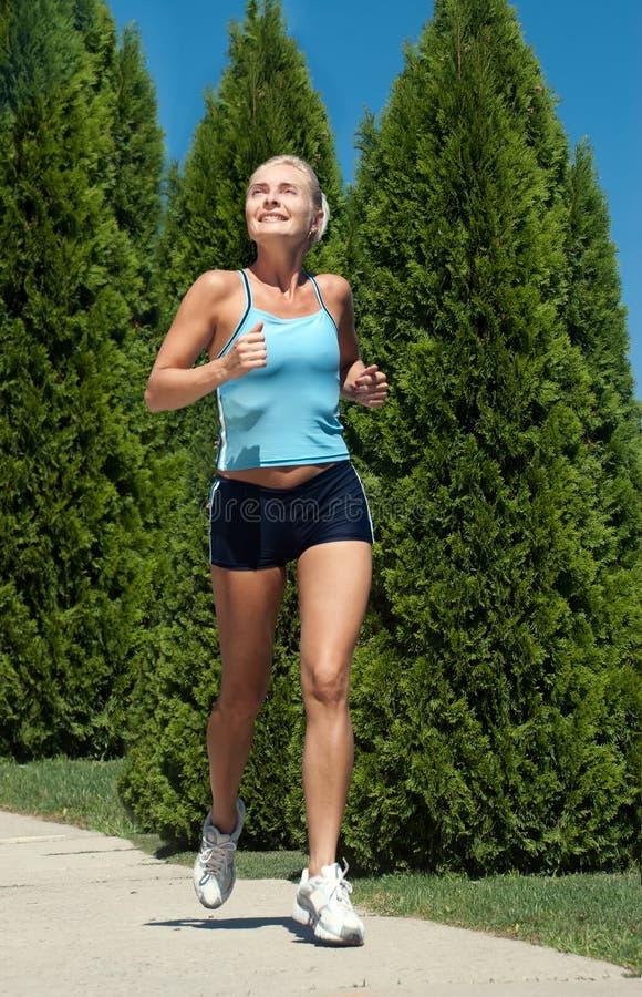 Mujer que se ejecuta en parque verde en día de verano asoleado foto de archivo
