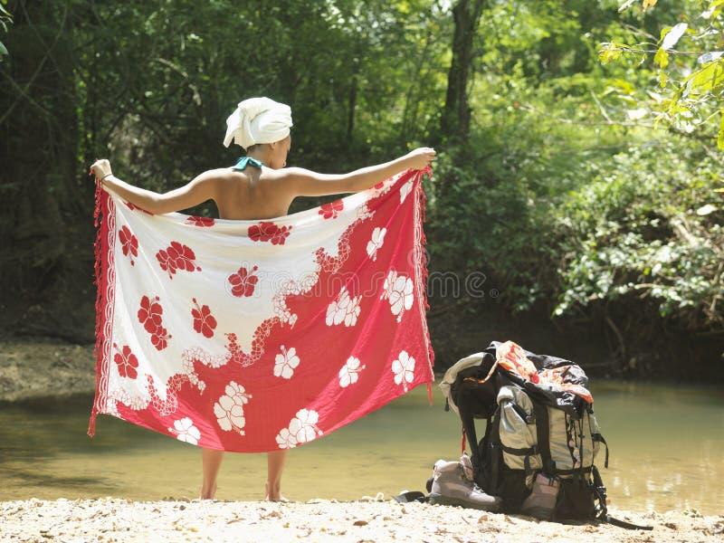 Mujer que se envuelve con los sarong por la mochila y el lago fotos de archivo libres de regalías
