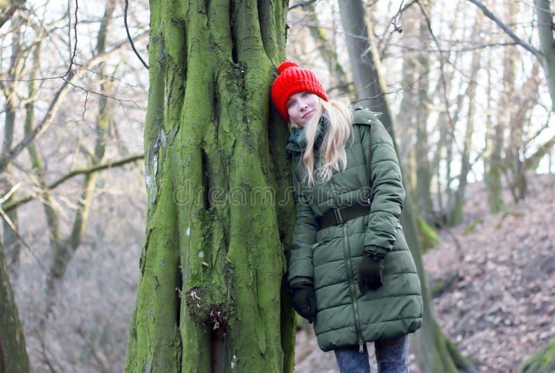 Mujer que se inclina contra árbol en bosque imágenes de archivo libres de regalías