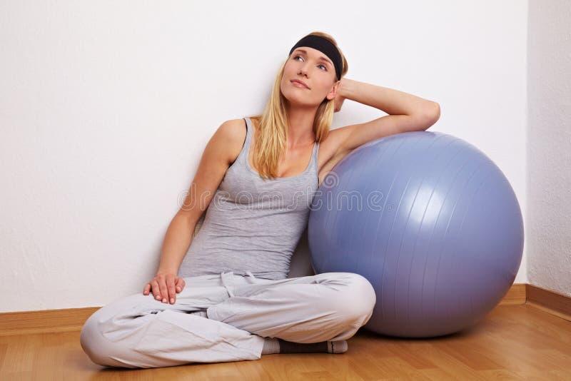 Mujer que se inclina en bola del gymn fotos de archivo