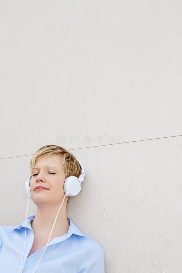 Mujer que se inclina en la pared que escucha la música fotos de archivo libres de regalías