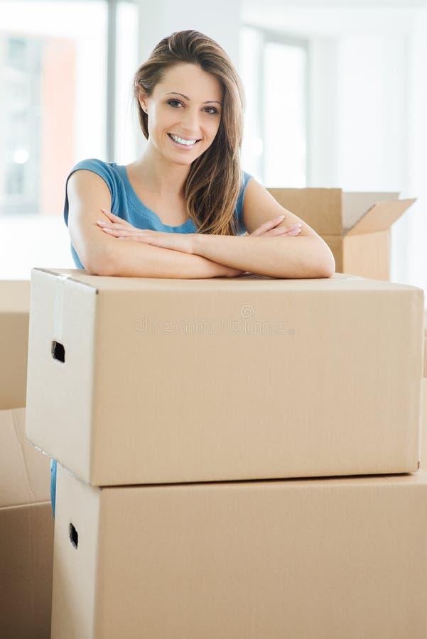 Mujer que se mueve en su nueva casa foto de archivo