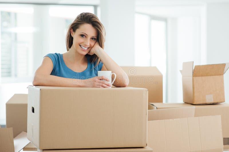 Mujer que se mueve en su nueva casa imagen de archivo