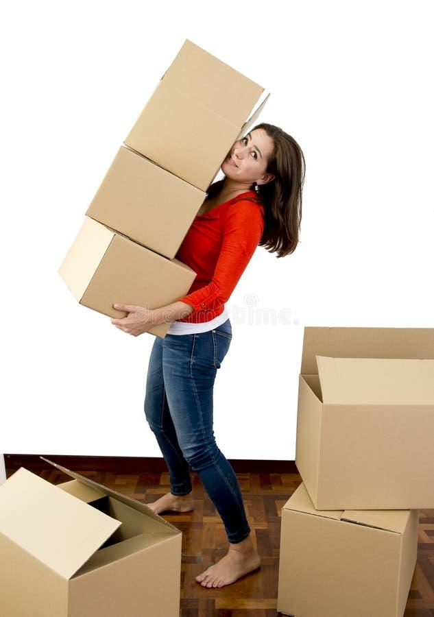 Mujer que se mueve en una pila que lleva de la nueva casa de cajas de cartón fotografía de archivo libre de regalías