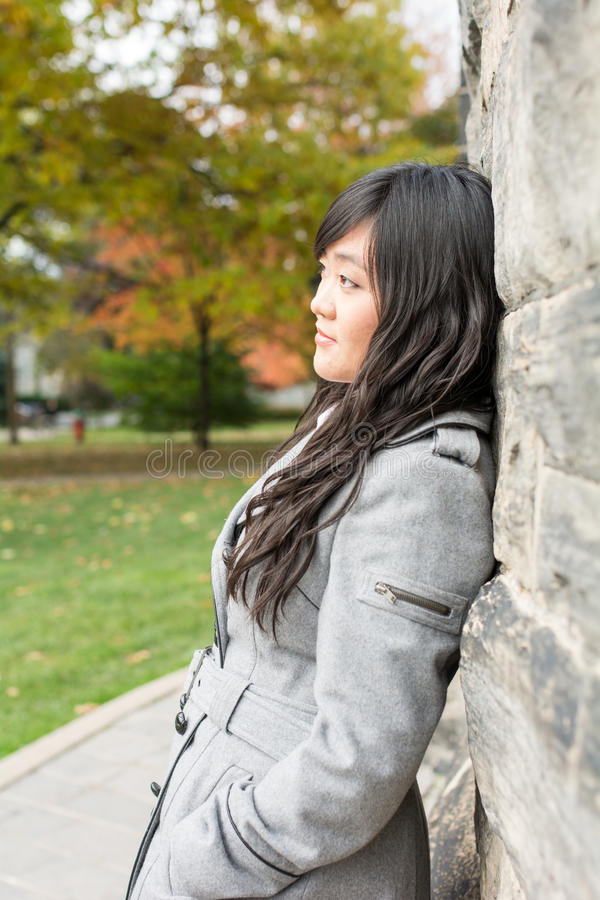 Mujer que se opone a una pared de ladrillo foto de archivo