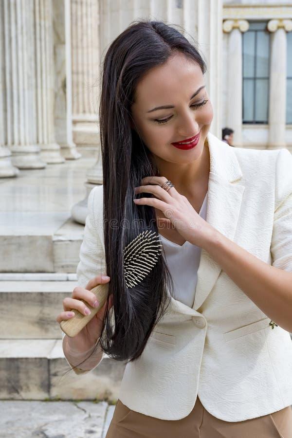 Mujer que se peina el pelo al aire libre fotografía de archivo
