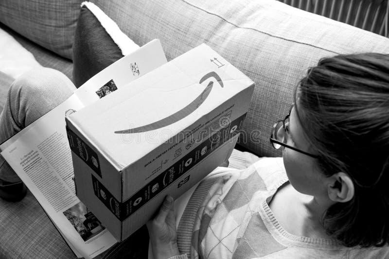 Mujer que se prepara para abrir la caja de cartón del Amazonas imagen de archivo libre de regalías