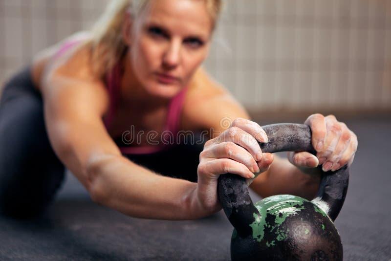 Mujer que se reclina durante el entrenamiento de Kettlebell imagen de archivo libre de regalías