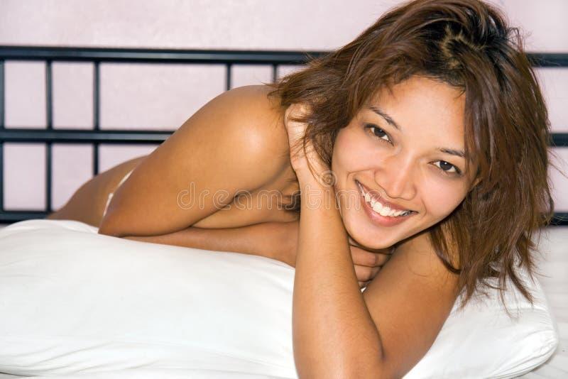 Mujer que se reclina en cama foto de archivo