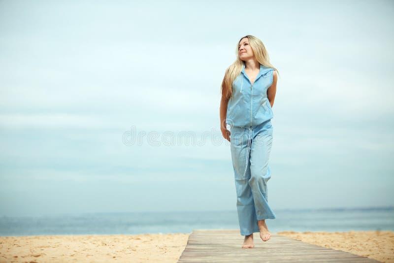 Mujer que se reclina en la playa imagen de archivo