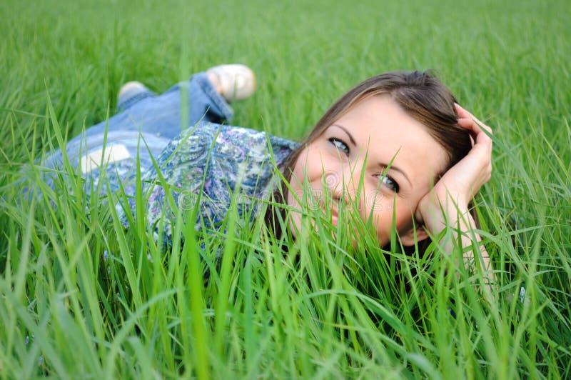 Mujer que se reclina sobre hierba foto de archivo libre de regalías