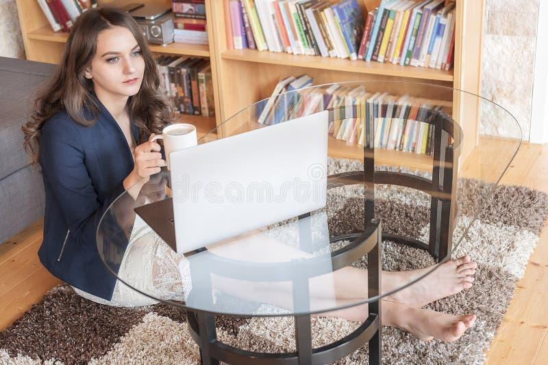 Mujer que se relaja con café y el ordenador portátil fotos de archivo