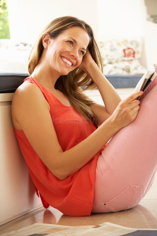 Mujer que se relaja con el periódico en el país imagenes de archivo