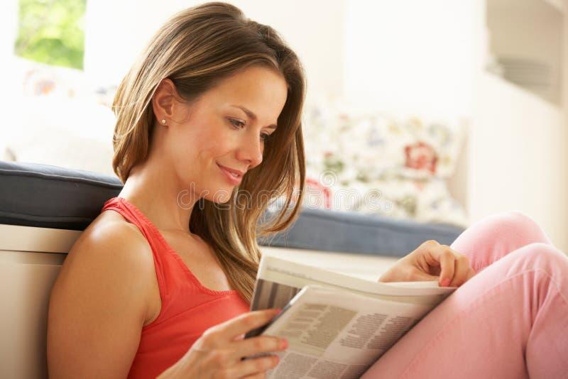Mujer que se relaja con el periódico en el país foto de archivo