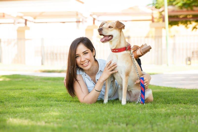 Mujer que se relaja con su perro en un parque fotografía de archivo libre de regalías