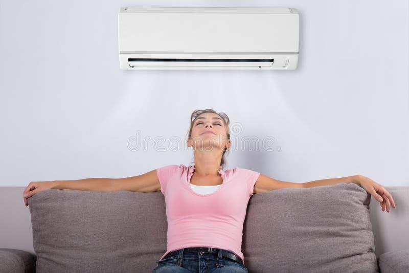 Mujer que se relaja debajo del acondicionador de aire imagen de archivo