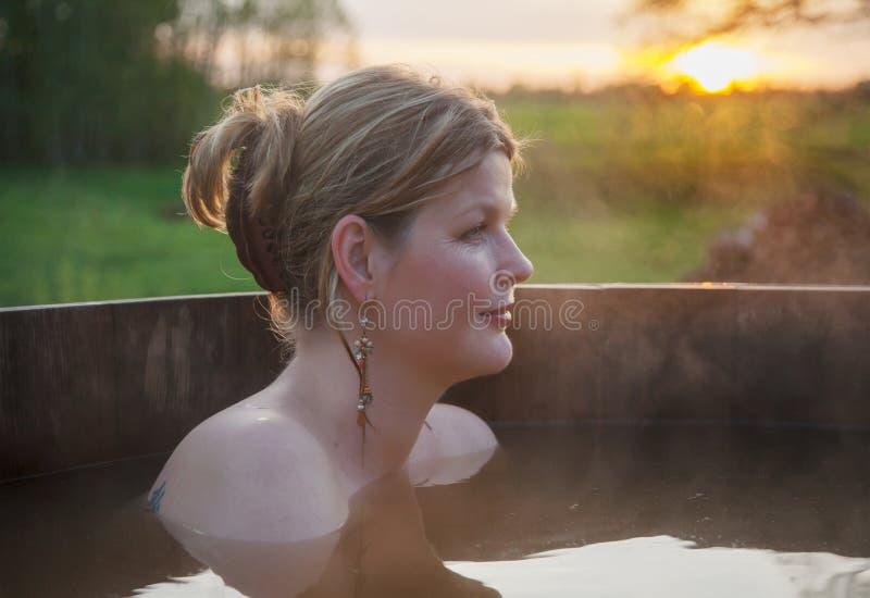 Mujer que se relaja en baño al aire libre en la puesta del sol foto de archivo libre de regalías
