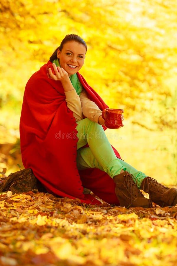 Mujer que se relaja en bebida de consumición del parque de la taza imagenes de archivo