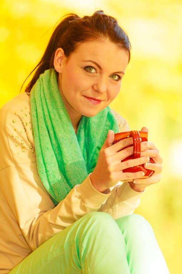 Mujer que se relaja en bebida de consumición del parque de la taza fotos de archivo