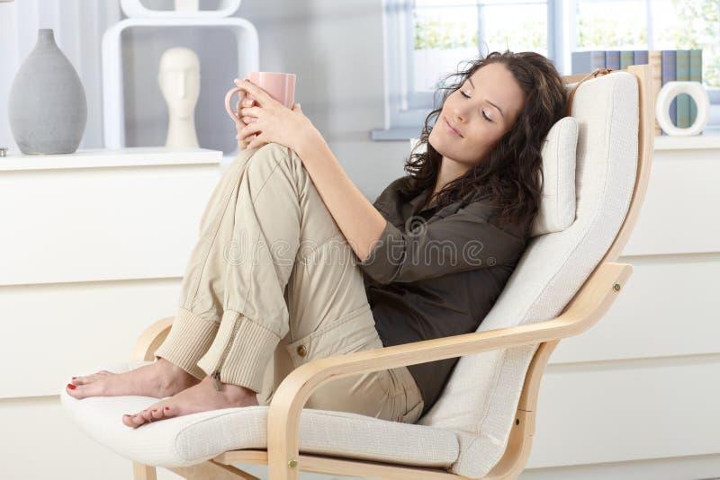 Mujer que se relaja en butaca fotografía de archivo