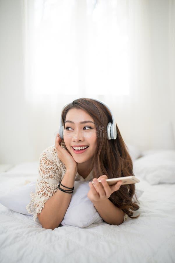 Mujer que se relaja en cama y que escucha la música, relajándose en su li imágenes de archivo libres de regalías