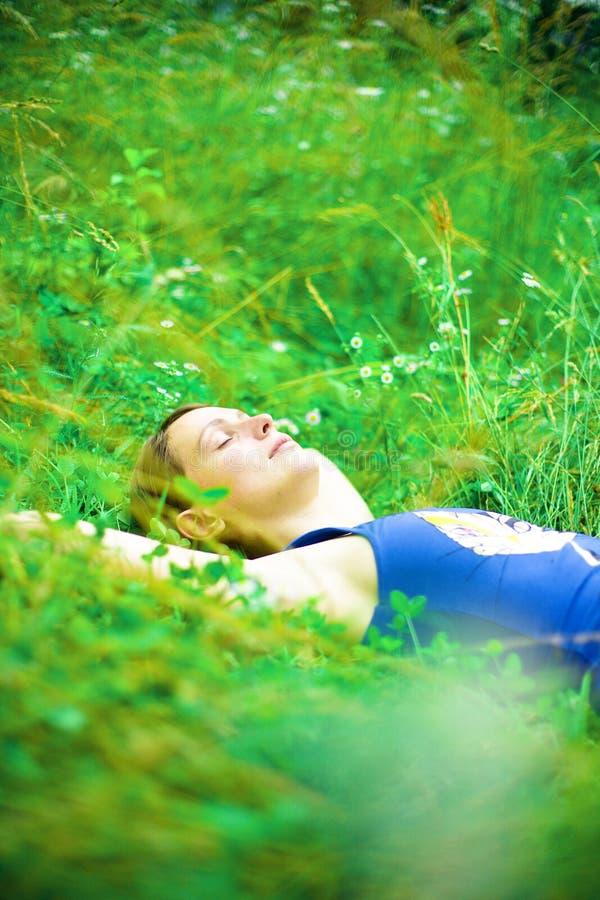 Mujer que se relaja en campo verde imagenes de archivo