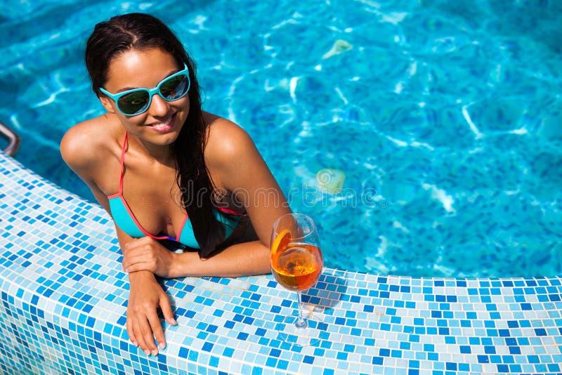 Mujer que se relaja en el agua de la piscina en día soleado caliente Summ foto de archivo