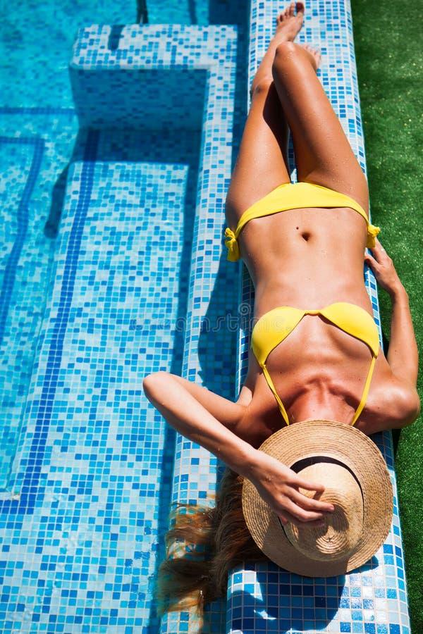 Mujer que se relaja en el agua de la piscina en día soleado caliente Summ fotografía de archivo
