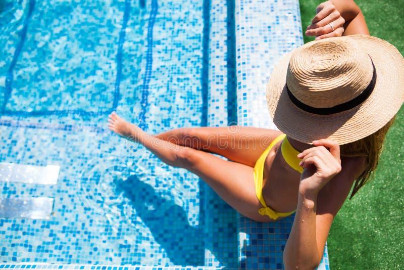 Mujer que se relaja en el agua de la piscina en día soleado caliente Summ imagenes de archivo