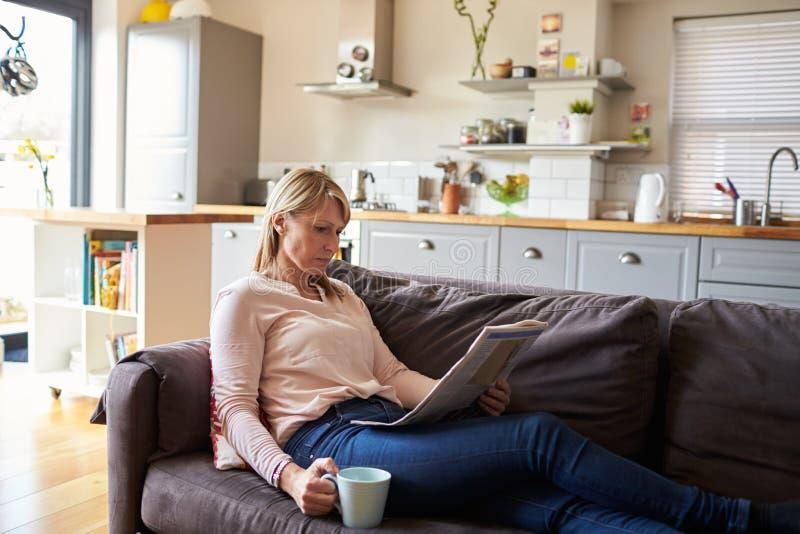 Mujer que se relaja en el apartamento de Sofa Reading Newspaper In Modern imagenes de archivo
