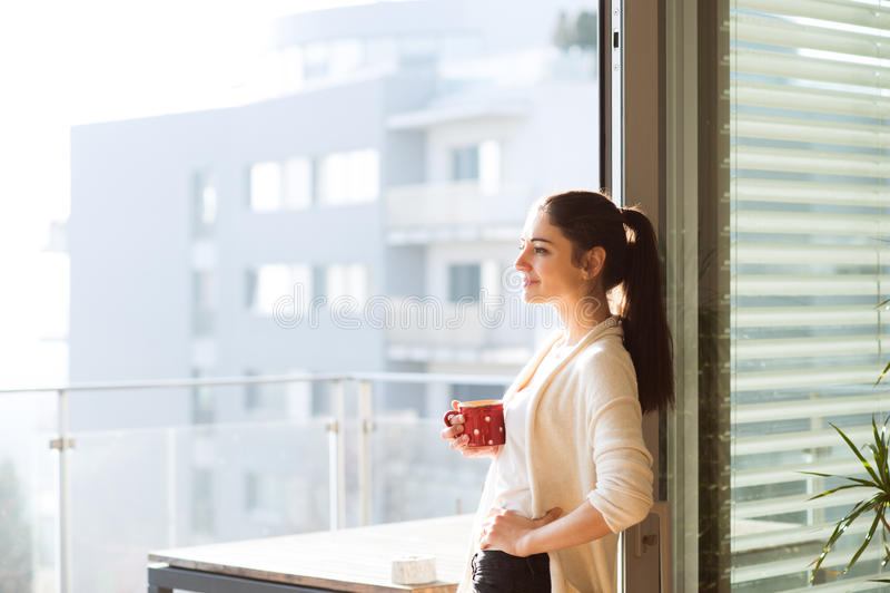 Mujer que se relaja en el balcón que sostiene la taza de café o de té imagenes de archivo