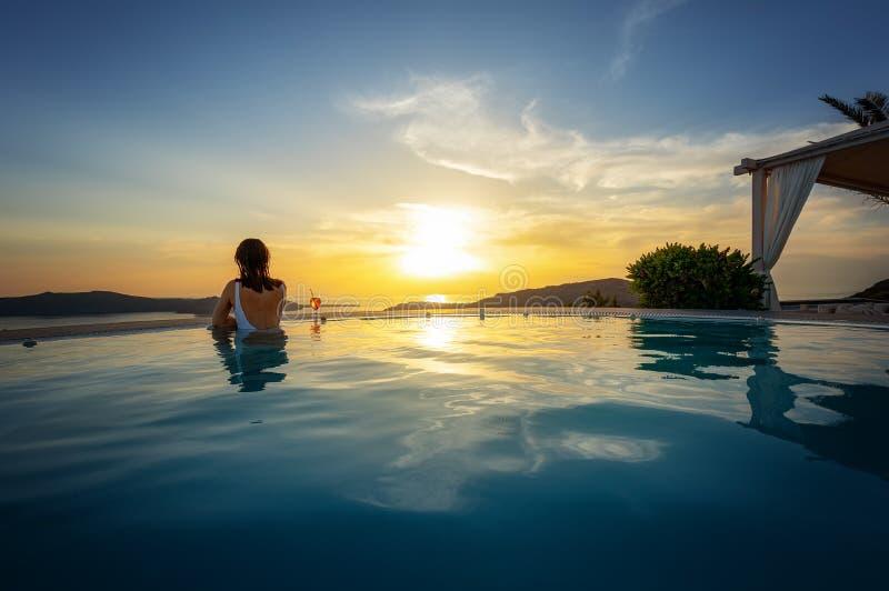 Mujer que se relaja en el borde de la piscina del infinito en la puesta del sol foto de archivo libre de regalías