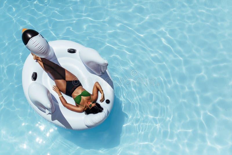Mujer que se relaja en el cisne inflable que flota en piscina fotos de archivo libres de regalías