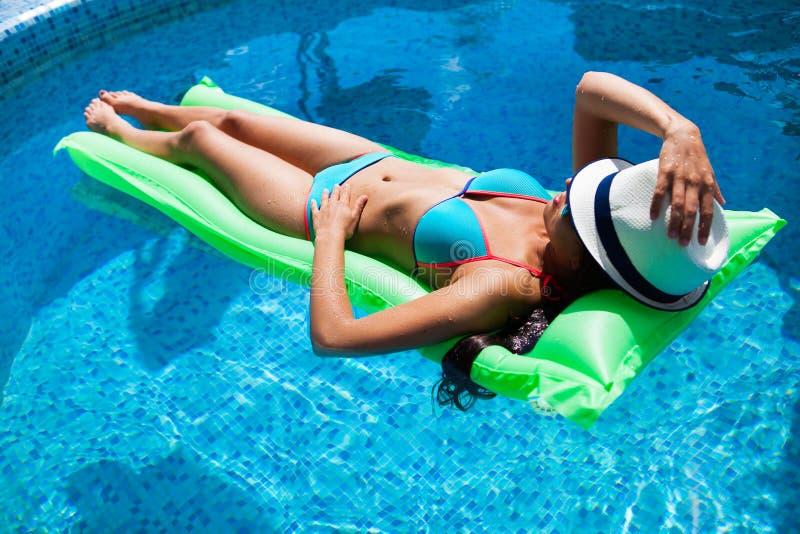 Mujer que se relaja en el colchón en el agua de la piscina en día soleado caliente S fotos de archivo libres de regalías