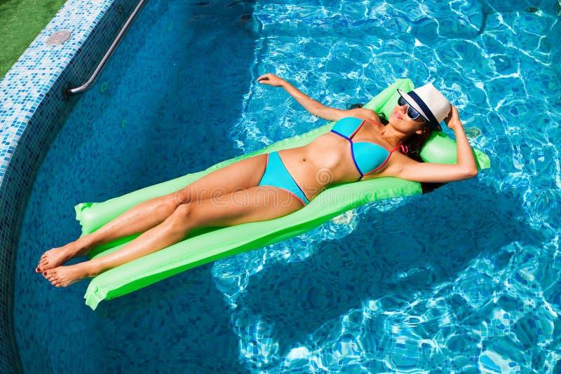 Mujer que se relaja en el colchón en el agua de la piscina en día soleado caliente S imágenes de archivo libres de regalías