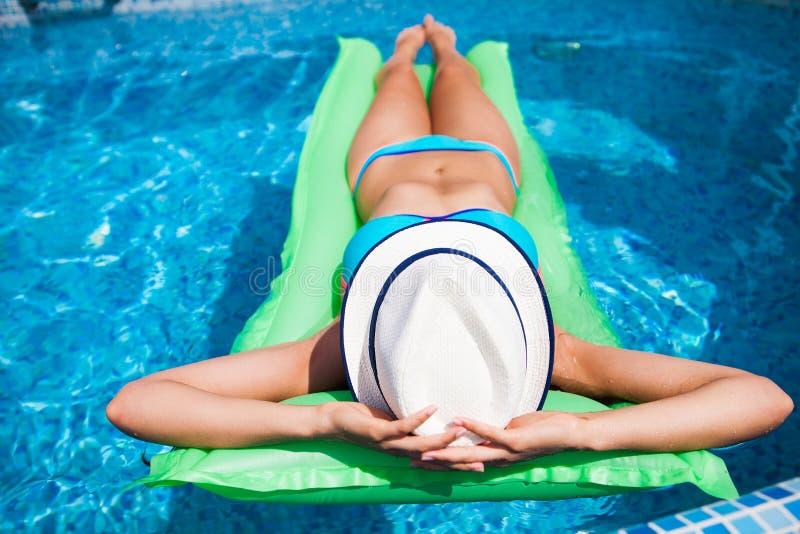 Mujer que se relaja en el colchón en el agua de la piscina en día soleado caliente S fotos de archivo