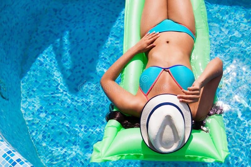Mujer que se relaja en el colchón en el agua de la piscina en día soleado caliente S fotografía de archivo