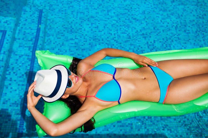 Mujer que se relaja en el colchón en el agua de la piscina en día soleado caliente S foto de archivo libre de regalías