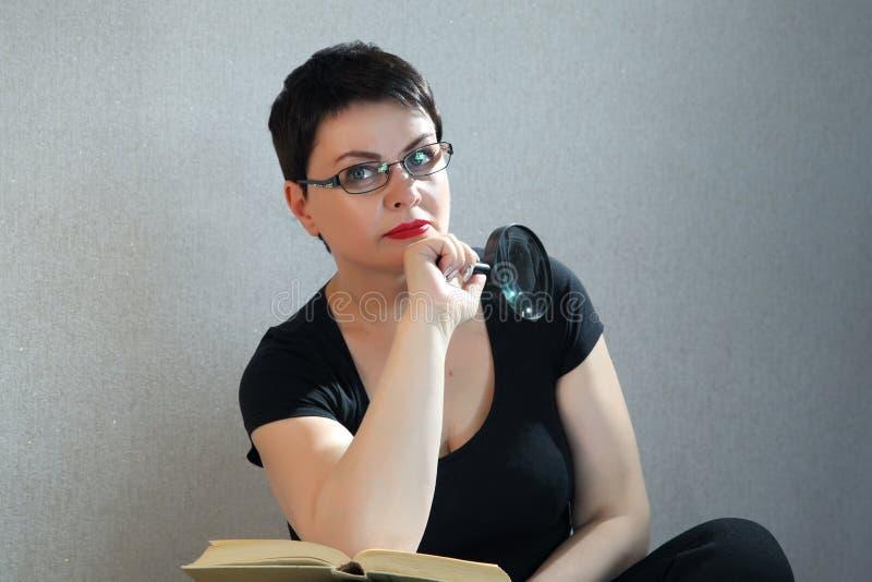 Mujer que se relaja en el libro de lectura del piso en casa imagenes de archivo