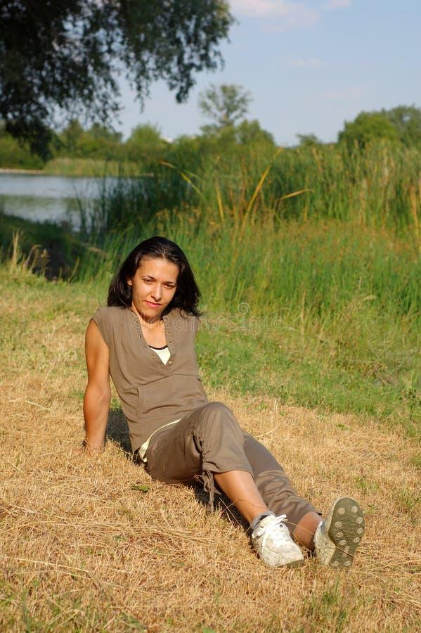 Mujer que se relaja en el parque imagenes de archivo