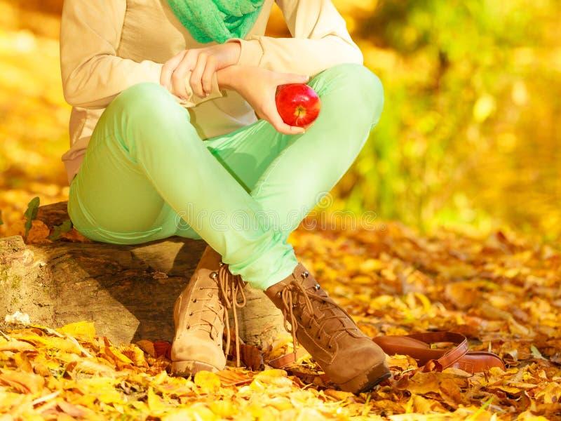 Mujer que se relaja en el parque que sostiene la fruta de la manzana imagen de archivo libre de regalías
