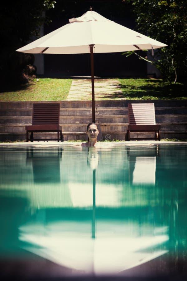 Mujer que se relaja en el salón de la piscina fotografía de archivo