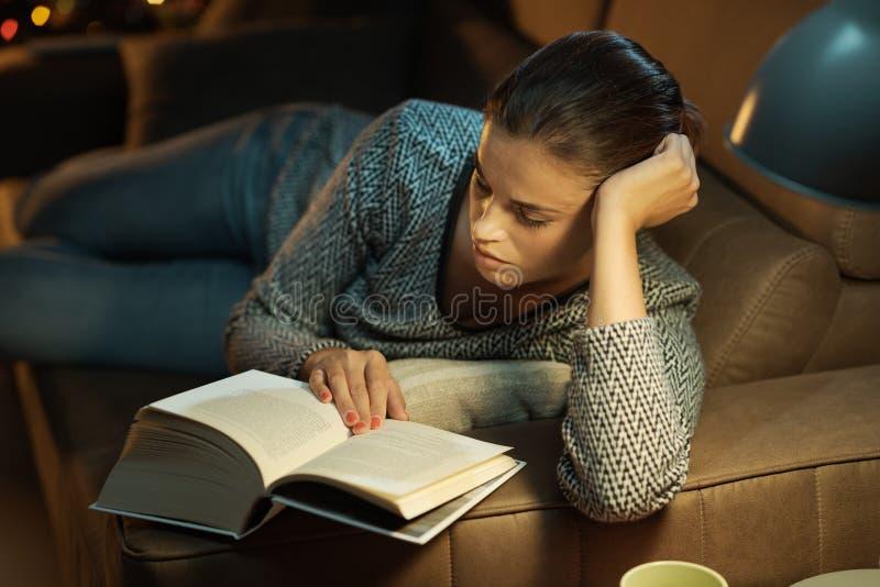 Mujer que se relaja en el sof? y la lectura imagen de archivo libre de regalías