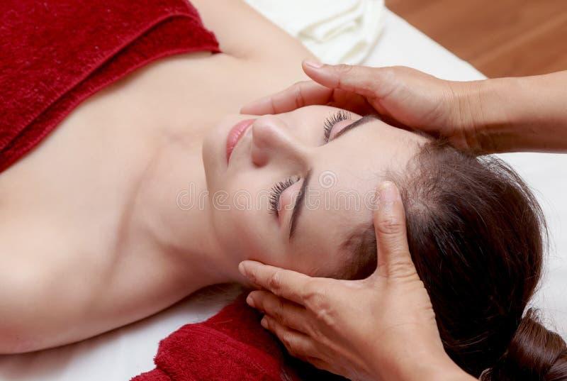 Mujer que se relaja en el tratamiento de la belleza, masaje facial imágenes de archivo libres de regalías