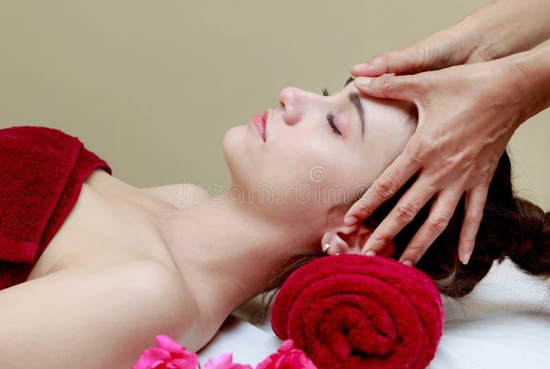 Mujer que se relaja en el tratamiento de la belleza, masaje facial foto de archivo libre de regalías